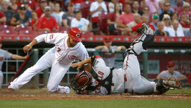 Cincinnati Reds shortstop Eugenio Suarez (left) is tagged out at home by Arizona Diamondbacks catcher Welington Castillo (right) in the second inning.