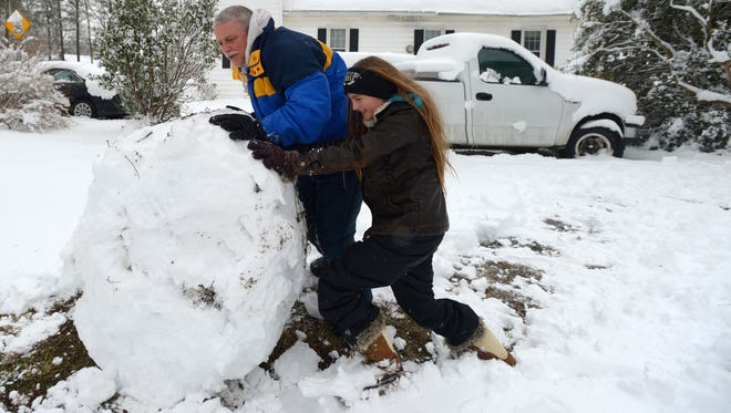 Mike Killebrew and his daughter Jessica begin the process of building a colossal snow man at their Cheriton, Va. home on Thursday, Feb. 26, 2015.