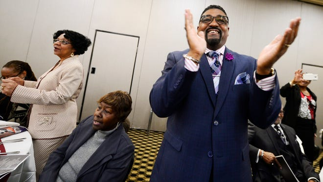 Carl Scott of York, center, and Minnie Green of York, left, stand and clap along as members of the Helen Thackston Charter School Gospel Choir sing during the Fourth Annual B.M.A. MLK Image Awards and Scholarships Luncheon at Wyndham Garden York in West Manchester Township.