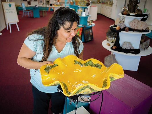 "Elizabeth Snow examines a decorative bowl by artist Cheryl Kilian-Hoffer at the Desert Roots Artists' Market & Gallery. The new arts emporium features works by more than 35 artists, snacks, special custom tea brews, art classes and a ""neighborhood hang-out."""