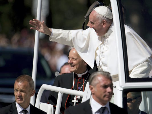 Pope Francis, joined by Cardinal Donald Wuerl, archbishop of Washington, waves from his popemobile during a parade around the Ellipse near the White House in Washington, Wednesday, Sept. 23, 2015. (AP Photo/Carolyn Kaster)