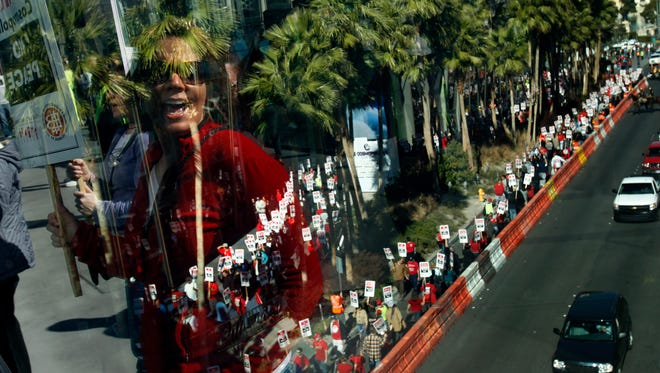 A culinary union member is reflected in a window chanting in protest in front of The Cosmopolitan hotel and casino on Jan. 31, 2013.