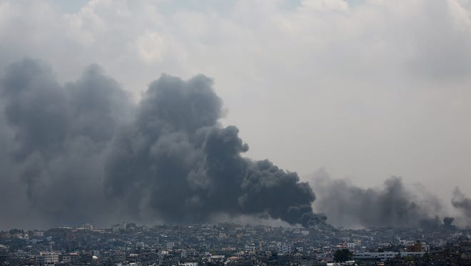 Smoke rises after an Israeli missile hit Shijaiyah neighborhood in Gaza City, northern Gaza Strip, Sunday, July 20, 2014. A Gaza City neighborhood came under heavy tank fire Sunday as Israel widened its ground offensive against Hamas, causing hundreds of residents to flee.