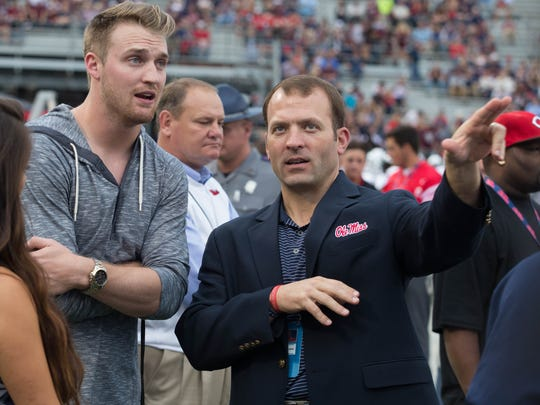 Ross Bjork talks to former Ole Miss quarterback Bo Wallace on the sideline at a football game.
