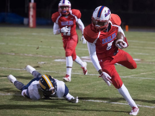 Pine Forest High's Jacob Copeland, (No.5) breaks the tackle of Gulf Breeze High's Walter Yates (No. 3) during the Region 1-6A playoff game Friday night.