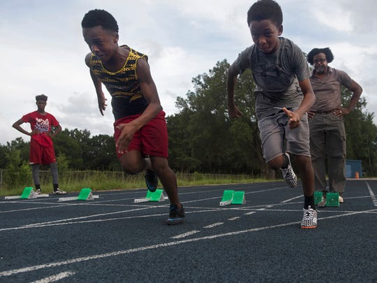 Golden Elite Track Club sprinters, Will Smith, Jr., center, and Julian Tillman, right, train under of the watchful eye of coach Rodney McGhee, background right, at Washington High School Tuesday afternoon, July 11, 2017.  the upcoming AAU Junior Olympics meet in Detroit. The local track club is preparing the upcoming AAU Junior Olympics in Detroit.