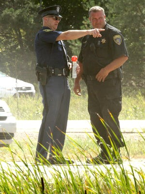 Police officials talk at the scene of a serious U.S. 23 crash confer as they begin to mark the scene with an eye toward further investigation in the wake of the incident.