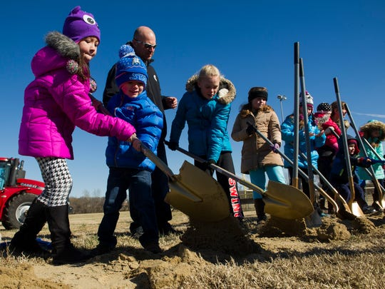 Adrianna Drake, 7, and her brother, Brody Drake, 4, both of McCutchanville, share a shovel during a groundbreaking ceremony for the new McCutchanville Elementary, just north of McCutchanville Park on Petersburg Road, Saturday, Feb. 4, 2017. The new school is expected to open for the 2018-19 school year.