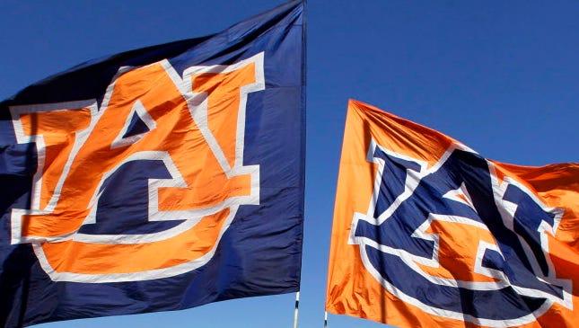 Auburn Tigers cheerleaders carry Auburn flags.