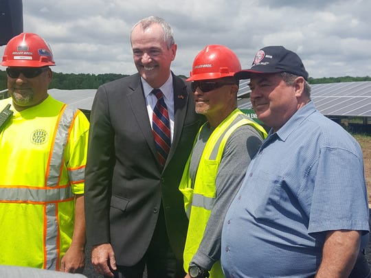 New Jersey Gov. Phil Murphy poses with electrical union members after signing a bill to subsidize Public Service Enterprise Group's two nuclear plants in Salem County.