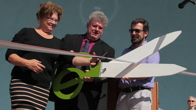 Robert Nueske, center, flanked by his wife Darlene Nueske and Wittenberg Village President Billy Switalla partcipate in a ribbon cutting at the rededication ceremony for the village's newly remodeled band shell on September 11, 2013.