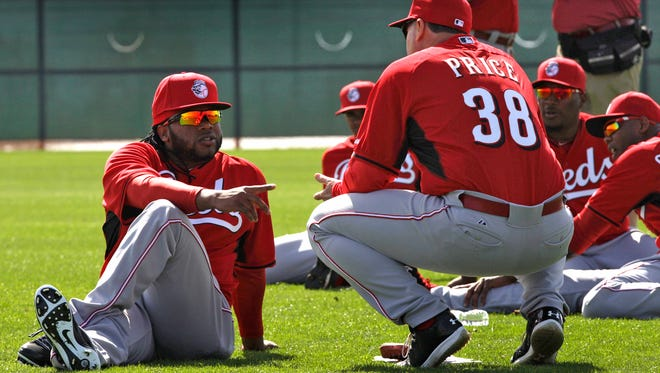 Reds pitcher Johnny Cueto stretches and talks with manager Bryan Price on Thursday morning in Goodyear.