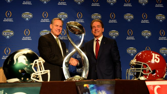 Michigan State head coach Mark Dantonio, left, and Alabama head coach Nick Saban shake hands by the Cotton Bowl trophy Wednesday, December 30, 2015, after a press conference at the Omni Hotel in Dallas. The two coaches and their teams will face off Thursday at 7 p.m. in the College Football Playoff semifinal game.