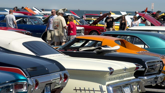 Car enthusiasts walk around Inlet Lot in Ocean City checking out all the cars on display during Cruisin' Ocean City.