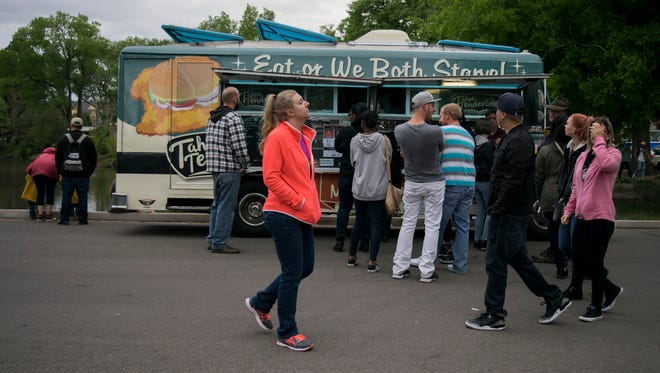 Folks attend the first Food Truck Friday event of the 2018 season on May 18. An average of about 30 food trucks set up shop each week at the event, organizers said.