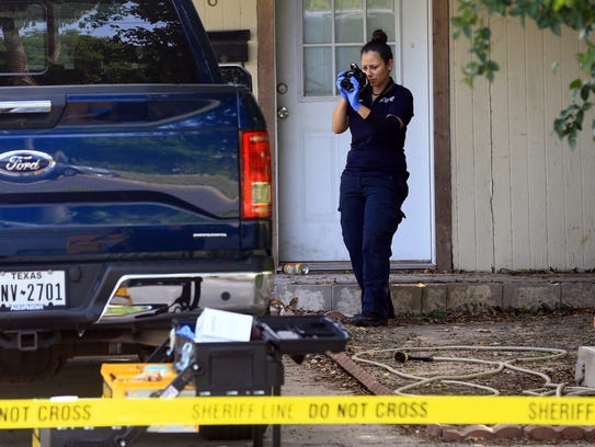 A Kingsville police officer investigates a home after