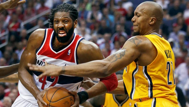 Washington Wizards forward Nene (42) of Brazil drives past Indiana Pacers forward David West (21) during the first half of Game 3 of an Eastern Conference semifinal NBA basketball playoff game in Washington, Friday, May 9, 2014. (AP Photo/Alex Brandon)