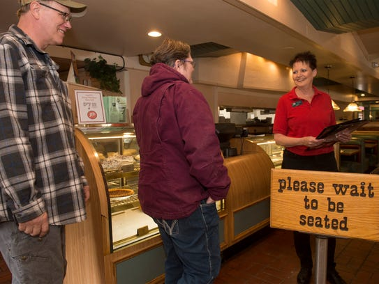 JB's restaurant server Sandy Ulmen, who has been with JB's for 37 years, seats customers on Wednesday morning.