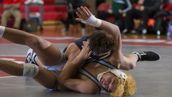 Howell, with Xavier Kell (top) y, as one of its improving wrestlers, cemented its status as the No. 1 ranked team in the Asbury Park Press Top 10 by winning the Shore Conference Tournament.