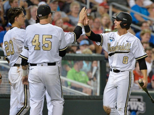 Vanderbilt's Rhett Wiseman (8) is greeted by Tyler Ferguson (45) and Bryan Reynolds (20) after he scored a run against on a single by John Norwood in the seventh inning Monday.