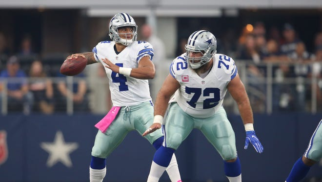 Dallas Cowboys quarterback Dak Prescott (4) throws the ball with center Travis Frederick (72) in the first quarter against Cincinnati Bengals at AT&T Stadium.