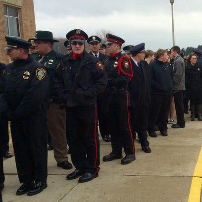 Mourners wait in line outside of Kiel High School for