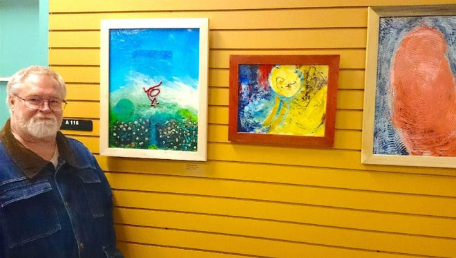 Paterson artist Michael Sherman stands by some of his paintings now on display at the Broadway Gallery of the Passaic County Community College.