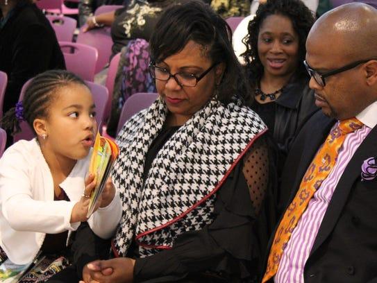 Iana NIckerson, 6, shows her parents, Sherita and Ian,