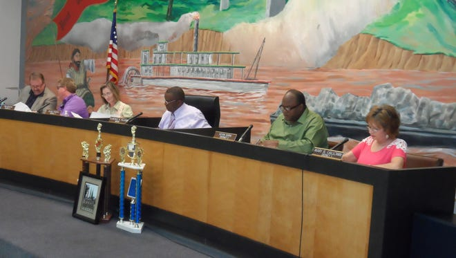 The Pineville City Council discusses city business during Tuesday night's council meeting. The council met in executive session and then authorized Mayor Clarence Fields (center) to negotiate a settlement of a $2.3 million debt to the Internal Revenue Service.