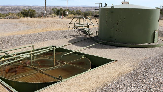A below-grade tank, front, that stores water from the oil tank, back, and three-phase separator, not pictured, as seen Friday March 11, 2016, at an XTO Energy natural gas well facility near Piedra Vista High School.