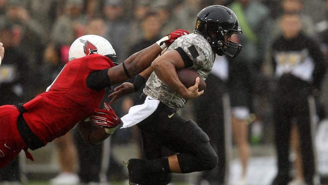 Oct 4, 2014; West Point, NY, USA; Army Black Knights quarterback Angel Santiago (3) is dragged down on a run by Ball State Cardinals defensive end Michael Ayers (9) during the first half at Michie Stadium. Mandatory Credit: Danny Wild-USA TODAY Sports