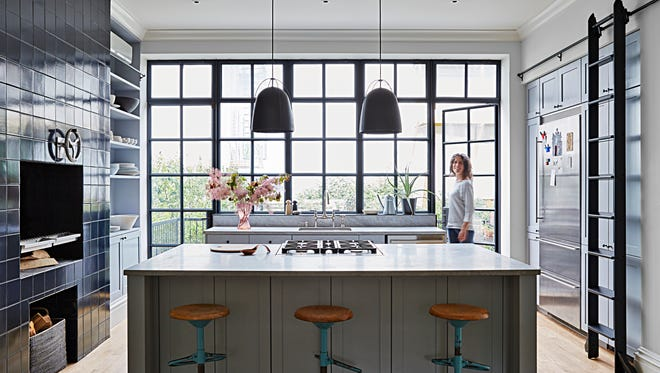 In their Brooklyn brownstone, Cristin Frodella (shown here) and her husband, Conor Sheridan, wanted a wide-open kitchen where everyone could gather — for breakfast, after-school snacks and dinners fired up on their indoor grill (far left).