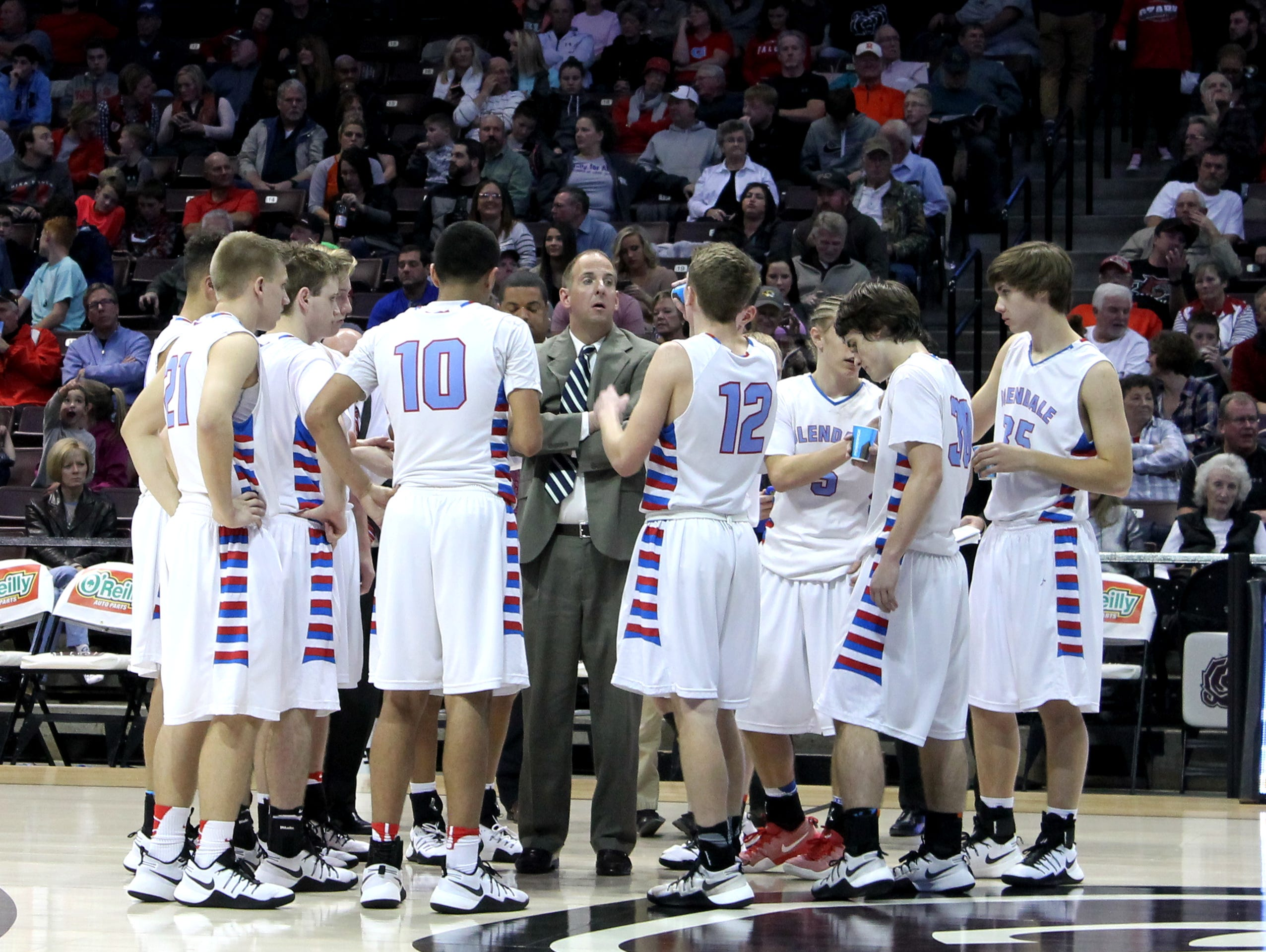The Glendale High School boys basketball team gathers around coach Brian McTague during a timeout of a Blue Division semifinal game with Hartville on Dec. 28, 2016 at JQH Arena.