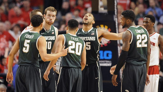 MSU's Bryn Forbes, Matt Costello, Travis Trice,  Denzel Valentine, and Branden Dawson, left to right, gather at the end of MSU's 80-69 overtime loss against Wisconsin in the Big Ten Tournament Championship game Sunday in Chicago.