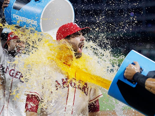 Texas Rangers' Brett Nicholas, center, is doused by Rougned Odor, right, and Elvis Andrus, left, after the team's 8-3 win over the Houston Astros in a baseball game Saturday, Aug. 12, 2017, in Arlington, Texas. (AP Photo/Brandon Wade)
