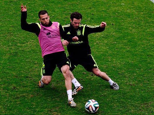 Spain's Jordi Alba, left, and Juan Mata duel for the ball during a training session at he Atletico Paranaense training center in Curitiba, Brazil, Tuesday, June 10, 2014. Spain will play in group B of the Brazil 2014 World Cup. (AP Photo/Manu Fernandez)