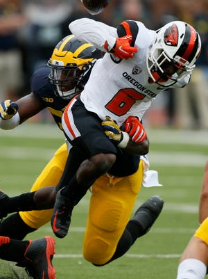 Michigan's Taco Charlton causes with his hit on Oregon State's Victor Bolden in the first half of Saturday's game at Michigan Stadium.