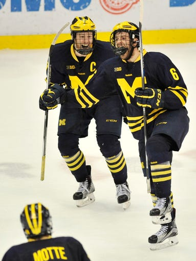 Michigan's JT Compher, left, and Sam Piazza (6) celebrate