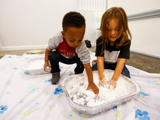 """One-year-old Zaiden Billy (left) and Julian Fewell, 3, play in """"snow"""" during a Ujima program meeting at the Bartley-Decatur Neighborhood Center on Wednesday, Dec. 13, 2017."""
