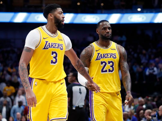 Los Angeles Lakers' Anthony Davis (3) and LeBron James (23) celebrate as they walk back to the bench in the final seconds of overtime in the team's  NBA basketball game against the Dallas Mavericks in Dallas, Friday, Nov. 1, 2019. The Lakers won 119-110. (AP Photo/Tony Gutierrez)