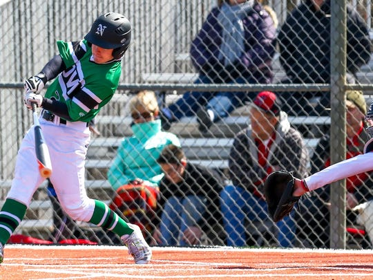 Novi's Spencer VanKirk makes contact at the plate in Saturday's second game of a twinbill against Troy Athens.