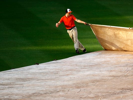 Sunlight shines on a groundskeeper as he helps to remove a tarp from the field during a rain delay before a baseball game between the Baltimore Orioles and the Cleveland Indians in Baltimore, Wednesday, June 21, 2017. (AP Photo/Patrick Semansky)