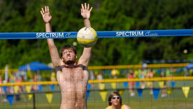 A player leaps to block a hit Sunday, July 26, during the annual Volleygrass volleyball tournament at Port Huron Northern.