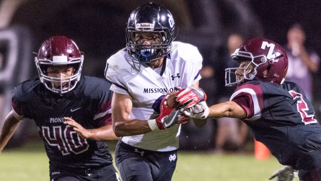 Mission Oak's Zach Wilson gets by Mt. Whitney's John Hadley in a non-league high school football game on Friday, September 7, 2018.