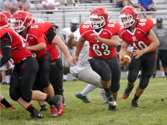 Riverheads #40 Harrison Schaefer carries the ball behind offensive lineman #63 Trenton Reid and the rest of this blockers  during their scrimmage against Appomattox High School in the Riverheads High School 2016 football jamboree on Aug. 20, 2016.