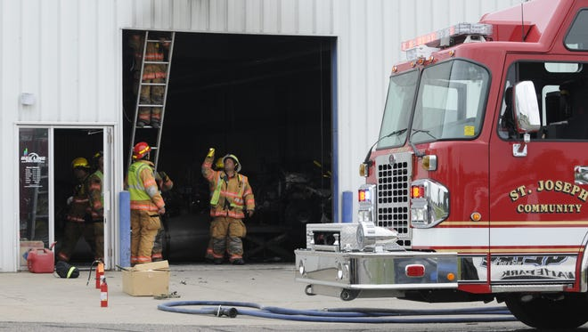 St. Joseph firefighters check for hot spots near a garage door at Bee Line Sports Center in St. Joseph on Tuesday, July 25.