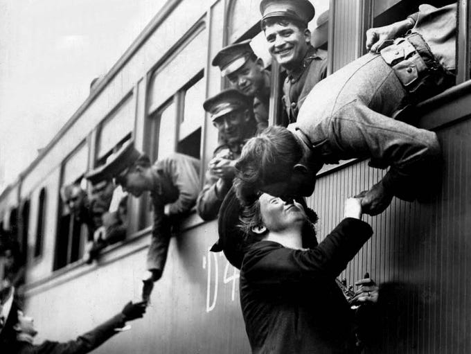 A solider tries to steal a kiss before his troop train