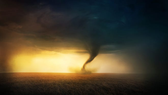 A tornado in a field at sunset.