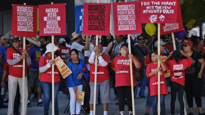Union workers and minimum wage activists gather for a Labor Day rally in downtown Los Angeles in 2017. California will raise its minimum wage to $14 an hour next year for workers at larger companies, hitting businesses with higher costs even at a time when many are struggling amid the coronavirus pandemic.