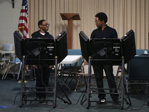 Wesley Bell Jr., 18, left, casts his vote alongside